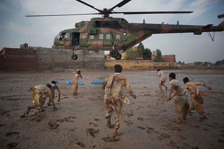 moradores-recolhem-garrafas-de-água-jogadas-pelo-exército-paquistanês,-Nowshera,-Paquistão,-2010